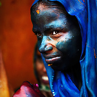 """A lady, covered in color herself, watching the other people playing with colors during the festival of """"Holi"""", India."""