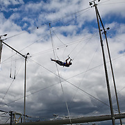 Student Danial Adkison practices a trick at Trapeze School New York during the June 4th morning class. The two hour beginner session taught the nine students in attendance the basics of flying trapeze -- including knee hangs and backwards somersaults -- in their facility on the roof of Pier 40...CREDIT: Daniella Zalcman for The Wall Street Journal.SLUG: NYMETROMONEY_Trapeze