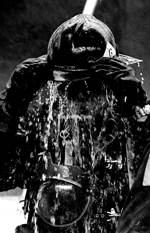 A tired and hot fire fighter found a way to cool off while fighting a stubborn blaze at the Poison Building at Western Avenue and Columbia Street. This fireman filled his hat with water and dumped it on his head. (Greg Gilbert / The Seattle Times, 1974)