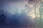 Abandoned playground at a hazy sunrise in fall - texturized photograph