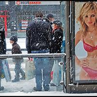 Nederland, Utrecht, 04-12-2010 - SINTERKLAAS INKOPEN -  Mensen in winterkleding staan met hun Sinterklaas inkopen tijdens een hevige sneeuwbui te wachten bij een bushalte in de Lange Viestraat naast een billboard met lingerie reclame van C en A met een foto van een jonge vrouw slechts gekleed bh en slipje. FOTO: Gerard Til