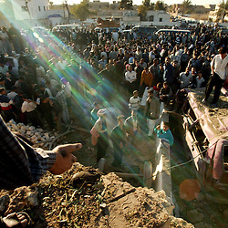 Iraqis crowd outside of the police station where a truck packed with an estimated 500 pounds of explosives blew up at a police station, Iskandariyah, Iraq, Feb. 10, 2004. Dozens of would-be recruits were lined up to apply for jobs. A hospital official said at least 50 people were killed and 50 others wounded. The local Iraqi police commander, Lt. Col. Abdul Rahim Saleh, said the attack was a suicide operation, carried out by a driver who detonated a red pickup as it passed the station.