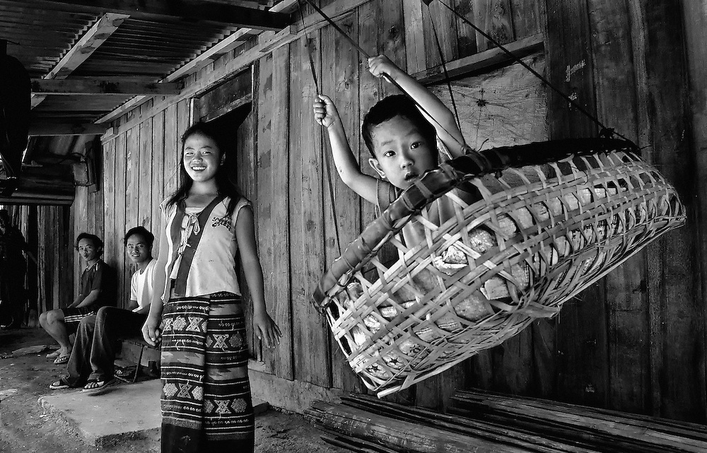 A cradle is used as a swing to entertain a young boy in a small village in Luang Prabang Province, Laos.