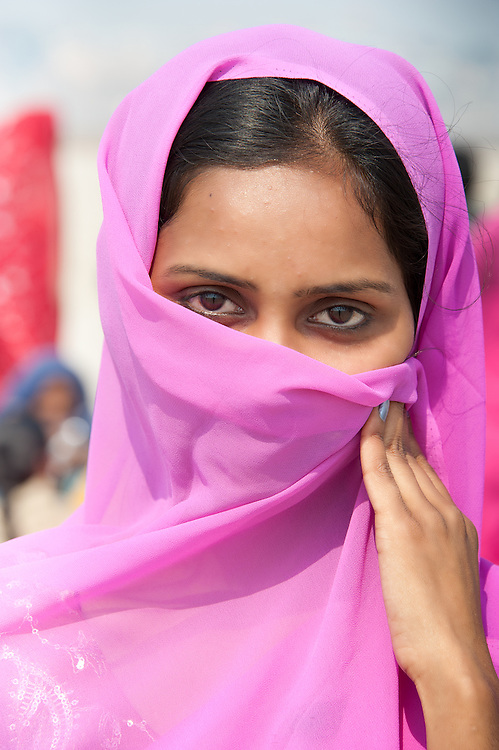 Portrait of a young Indian woman covering her face with a pink sari (Varanasi, India)