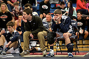 Coach Andrew Steedman and Luke Mendicino, a sophomore at Granville watch as a teammate takes to the mat in a wrestling match at the Granville Invitational season opener.