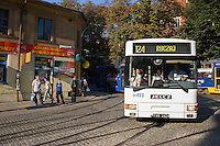 white articulated bendy bus full of people on a sunny afternoon in november, negotiates corner on the edge of krakow's old town with students and locals waiting at crossing