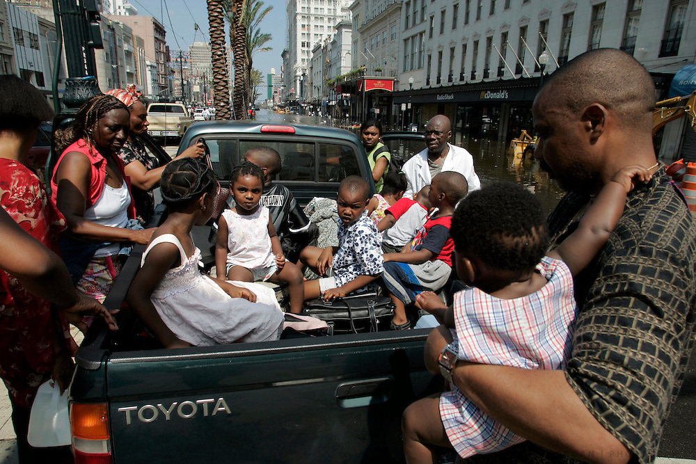 Fidelis Okonkwo, right, holds his 7-month-old daughter Obina as he and his family load into a pickup truck Wednesday, August 31, 2005, on Canal Street in New Orleans, La. Scott Morgan