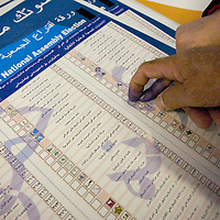 An Iraqi man points to names on the mock election ballot outside the voting area at the 2005 Iraqi Election in New Carrolton, Maryland, January 30, 2005. The poling site at a Ramada Inn next to Washington D.C.'s Capital Beltway is the only place for Iraqis living in the Northeast and Mid-Atlantic to vote. There are four other polling places - in Los Angeles, Detroit, Chicago and Nashville. Officials from the International Center for Migration, which is running the overseas voting for the Iraqi government, predict that roughly 22,000 Iraqis will vote at the Washington location.  Corbis Photo Ken Cedeno