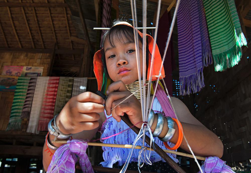 A Karen girl spinning cotton in a village in northern Thailand.