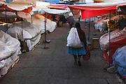 Woman walking through city market, Sucre, Bolivia