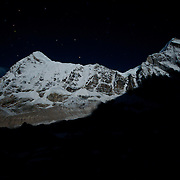 Pumori & Lingtren glow under a full moon as viewed from Khumbu Basecamp on Mount Everest, Nepal.