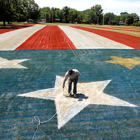 "Dano Bird, an employee of K and B Striping, paints one of the 50 stars in a three acre American flag in preparation for the Fourth of July. aekdb ""Larger Than Life"""