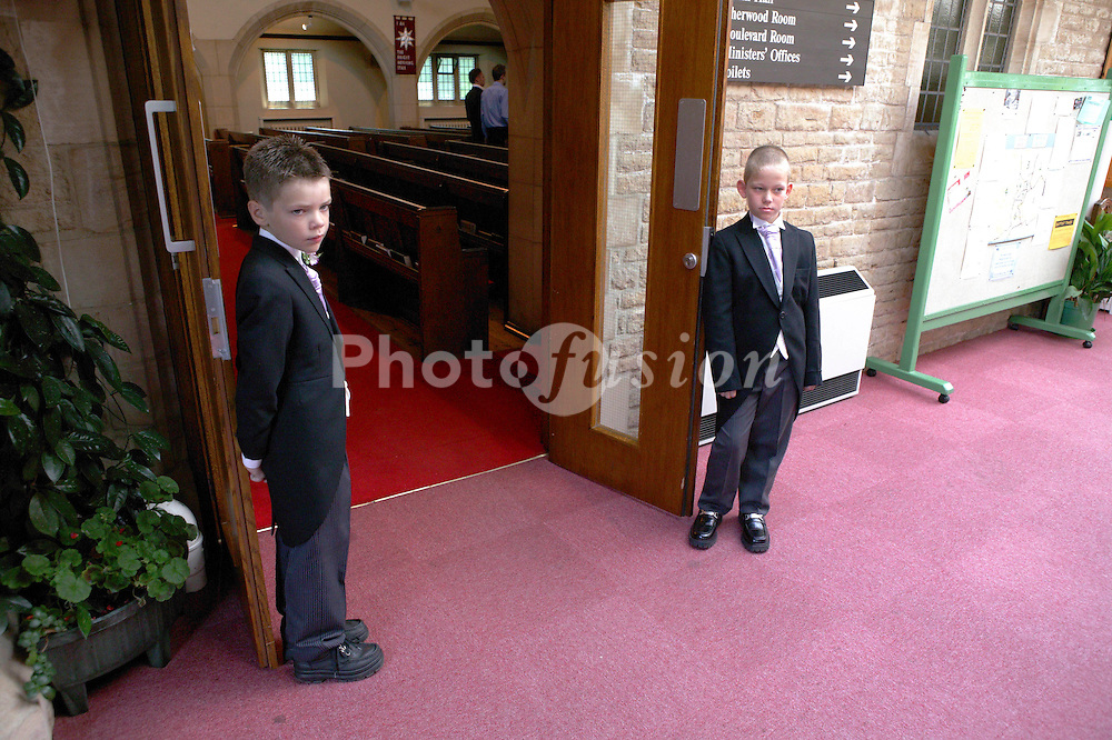Two young pageboys wearing suit tails standing at entrance to church,