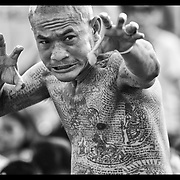 A devotee works himself into a trance during festivities at the Wat Bangpra Tattoo Festival in  Nakhon Chaisi