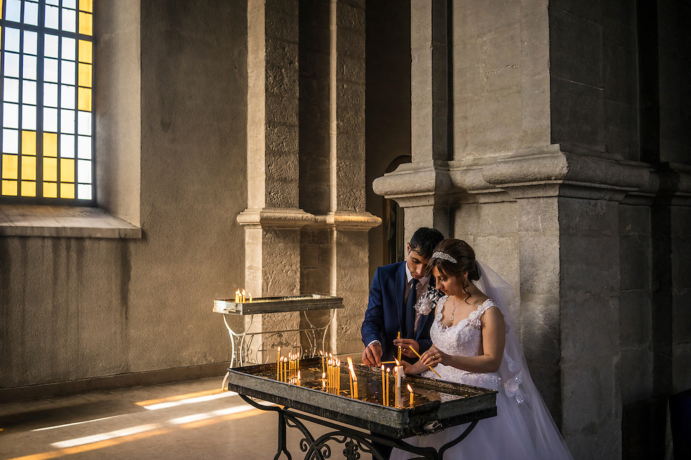 SHUSHI, NAGORNO-KARABAKH - APRIL 18: Groom Davit Simonyan, 24, and bride Shogher Hovsepyan, 25, light candles in prayer after their wedding at Ghazanchetsots church on April 18, 2015 in Shushi, Nagorno-Karabakh. Since signing a ceasefire in a war with Azerbaijan in 1994, Nagorno-Karabakh, officially part of Azerbaijan, has functioned as a self-declared independent republic and de facto part of Armenia, with hostilities along the line of contact between Nagorno-Karabakh and Azerbaijan occasionally flaring up and causing casualties. (Photo by Brendan Hoffman/Getty Images) *** Local Caption *** Davit Simonyan;Shogher Hovsepyan