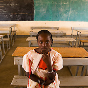 """Adjatou Traoré, 13, sits in a classroom at the Petit Paris primary school in the town of Dori, 240 km northeast of Burkina Faso's capital Ouagadougou on Monday May 11, 2009. When she was 12, Adjatou's mother attempted to sell her to a Ghanaian man who was trying to find his son a wife. She refused the marry the man. """"Early marriage is not a good thing,"""" she says, """"because a child should never have to give up school."""""""