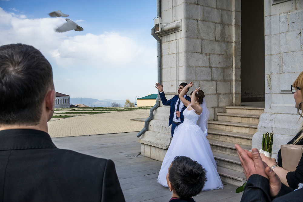 SHUSHI, NAGORNO-KARABAKH - APRIL 18: Groom Davit Simonyan, 24, and bride Shogher Hovsepyan, 25, release birds after their wedding at Ghazanchetsots church on April 18, 2015 in Shushi, Nagorno-Karabakh. Since signing a ceasefire in a war with Azerbaijan in 1994, Nagorno-Karabakh, officially part of Azerbaijan, has functioned as a self-declared independent republic and de facto part of Armenia, with hostilities along the line of contact between Nagorno-Karabakh and Azerbaijan occasionally flaring up and causing casualties. (Photo by Brendan Hoffman/Getty Images) *** Local Caption *** Davit Simonyan;Shogher Hovsepyan