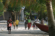 "Walking home from ""school closing"" festivities and life on Han Island, Carterets Atoll, Papua New Guinea, on Monday, Dec. 11, 2006.  Rising sea levels have eroded much of the coastlines of the low lying Carteret islands (situated 80km from Bougainville island, in the South Pacific), and waves have crashed over the islands flooding and destroying what little crop gardens the islanders have. Food is in short supply, banana and swamp taro crops are failing due to the salt contamination of the land, and the islanders live on a meagre one meal per day diet of fish and coconut. There is talk by the Autonomous Region of Bougainville government to relocate the Carteret Islanders to Bougainville island, but this plan is stalled due to a lack of finances, resources, land and coordination."