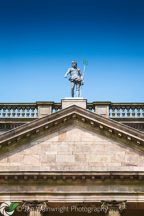 A statue of Neptune, trident in hand, stands on the roof of the south front of Lyme Park, Disley, Cheshire.
