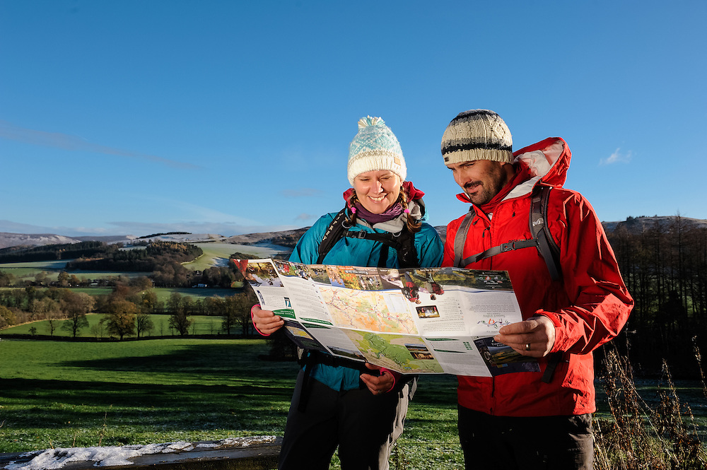 Walkers with map in Cademuir,  Tweed Valley, Forestry Commission, Scotland