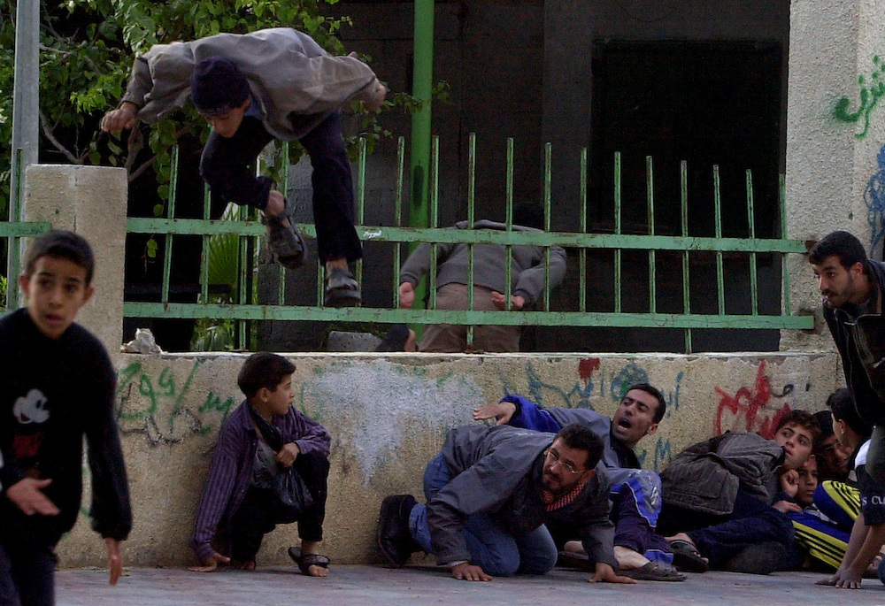 Palestinian children are caught in the crossfire as they duck, jump and flee from Palestinian police fire during a gunbattle that broke out between the Palestinian authority police and militant groups Hamas and  Islamic Jihad during a funeral procession in Jebaliya refugee camp in the northern Gaza Strip Friday Dec. 21, 2001.