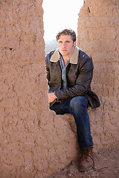 All American rugged man sitting on an adobe wall in New Mexico