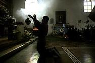 A man burns incense during Sunday mass at the Peroquia de Santo Christo church in Zacualpa, Guatemala.