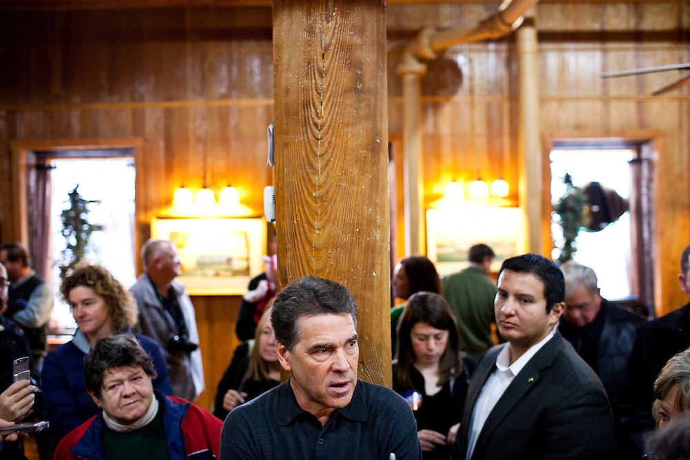 Republican presidential candidate Rick Perry, center, speaks to supporters at a meet and greet at Drake on the Riverfront restaurant on Thursday, December 22, 2011 in Burlington, IA.
