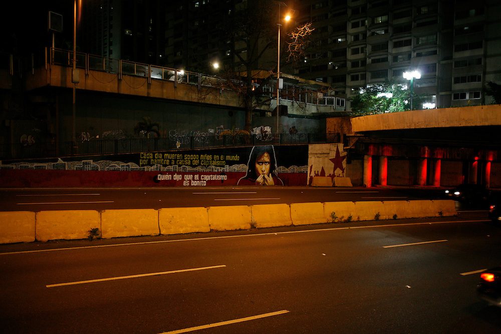 """A pro-Chavez mural seen on an empty highway at night that reads: """"Every day 50,000 children in the world, die of hunger as a cause of capitalism. Whoever said that capitalism was good."""""""