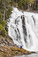 Man standing next to large waterfall in Prince William Sound in Southcentral Alaska. Spring. Afternoon.
