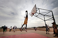 A member of the Bentiu state basketball team dunks in Bentiu on a court funded by oil money. Many people come to the town thinking there will be jobs and opporunities, but so far none of the oil wealth has trickled down to the people.