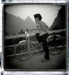 Young boy standing on the side of a road with his bicycle. Mountainous landscape of North Vietnam, Asia
