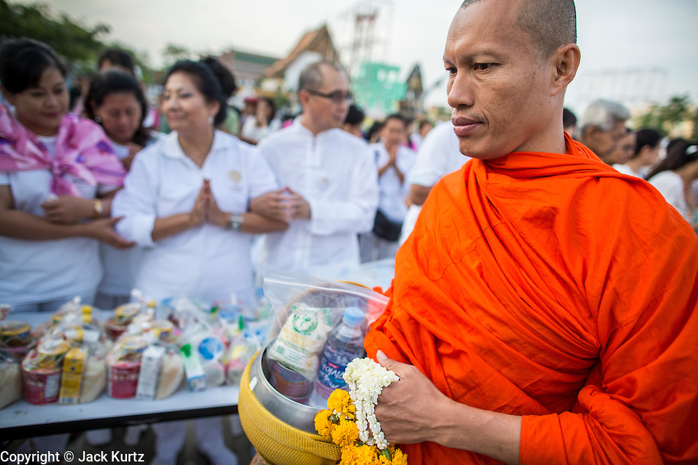 "01 JANUARY 2013 - BANGKOK, THAILAND:  Buddhists dressed in white present offerings to monks during a special merit making ceremony at Bangkok City Hall New Year's morning. Many Thais go to Buddhist temples and shrines to ""make merit"" for the New Year. The traditional Thai New Year is based on the lunar calender and is celebrated in April, but the Gregorian New Year is celebrated throughout the Kingdom.     PHOTO BY JACK KURTZ"