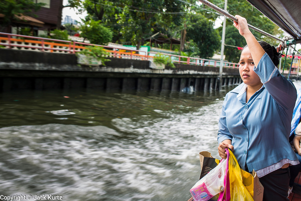 14 NOVEMBER 2012 - BANGKOK, THAILAND:  A passenger watches Bangkok go by while she rides the Khlong Saen Saeb passenger boat. Bangkok used to be criss crossed by canals (called Khlongs in Thai) but most have been filled in and paved over. Khlong Saen Saeb is one of the few remaining khlongs in Bangkok with regular passenger boat service. Boats and ships play an important in daily life in Bangkok. Thousands of people commute to work daily on the Chao Phraya Express Boats and fast boats that ply Khlong Saen Saeb. Boats are used to haul commodities through the city to deep water ports for export.      PHOTO BY JACK KURTZ