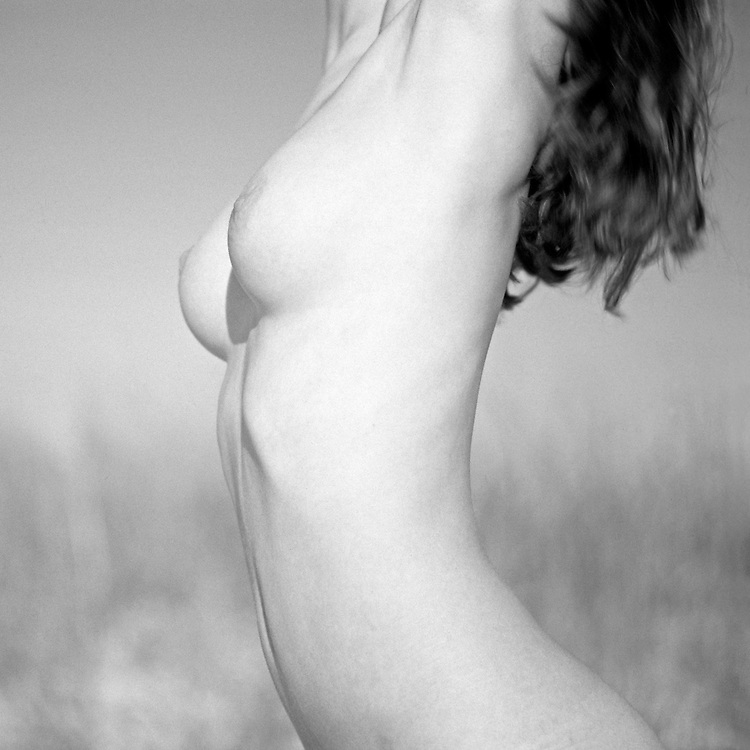 Naked young woman at the beach torso