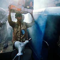 Pollution and over-crowded: porter stuck in traffic jam shrouded by exhaust smoke, in market area of Old Delhi..