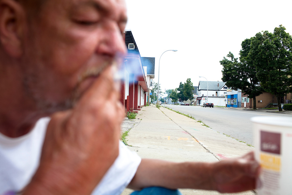 Clifford, a transient alcoholic, smokes a cigarette and panhandles in South Buffalo, NY, on Wednesday, July 29, 2009.