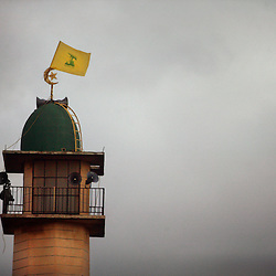 A Hezbollah flag flies above a mosque, Kfar Kila, Lebanon, March 10, 2005. Earlier in the week, hundreds of thousands of pro-Syrian protesters answered the nationwide call from Hezbollah, the militant Shiite Muslim group, to demonstrate against foreign intervention.