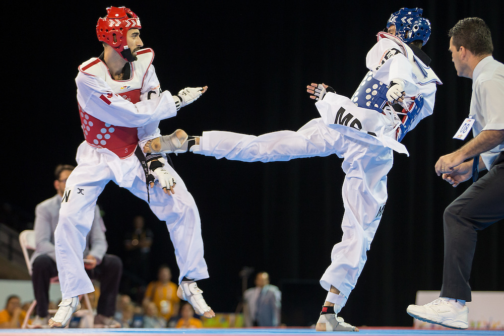 Saul Gutierrez (R) of Mexico kicks Maxine Potvin of Canada during their gold medal contest in the men's Taekwondo -68kg division of at the 2015 Pan American Games in Toronto, Canada, July 20,  2015.  AFP PHOTO/GEOFF ROBINS