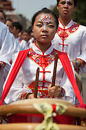 A female student from the Taipei School of Performing Arts plays a drum during a festial to honor the birthday of the Bao Sheng Emperor.