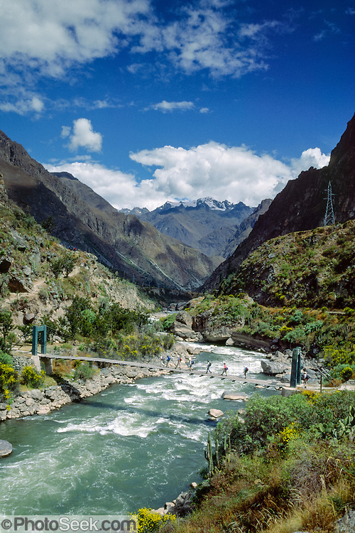Trekkers begin a 4-day version of the Inca Trail to Machu Picchu at this bridge over the Urubamba/Vilcanota River Valley, Sacred Valley of the Incas (7700 feet elevation) at railroad Kilometer 82, on the PeruRail route from Cusco to Machu Picchu, Cordillera Vilcabamba, Andes mountains, Peru, South America. Licensed by National Geographic Maps for a Geotourism Map of Peru's Sacred Valley, 2008.