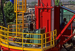 Stock photo of a man operating machinery at the base of a crane.