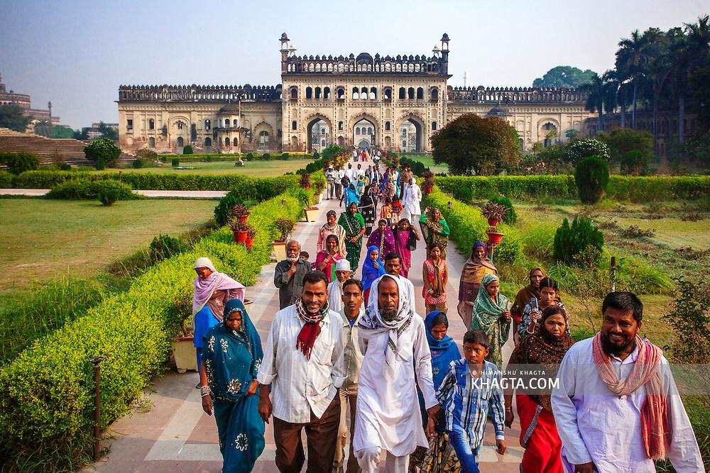 Indian tourists in the Imambara complex walking towards the Bara Imamabara Lucknow, Uttar Pradesh, India.  Imambara is a shrine built by Shia Muslims for the purpose of Azadari.
