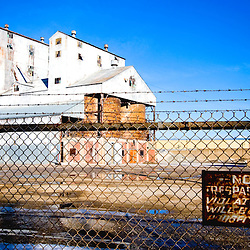 "An old glass factory stands empty, guarded by ""No Trespassing"" signs and barbed wire."