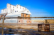 """An old glass factory stands empty, guarded by """"No Trespassing"""" signs and barbed wire."""