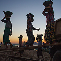 Women loading gravel from the Ayeyarwaddy River onto trucks near Bagan in Myanmar.