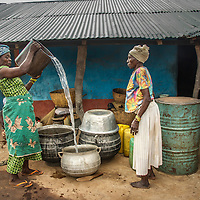 In a Ghanaian village without a well, women haul their own water first from a local stream, and then bring some to the chief's home as a sign of respect.