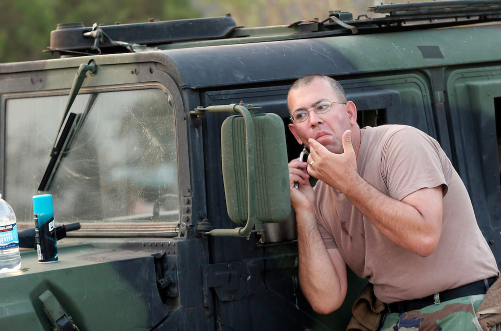 "Staff Sgt. ""Mac"" McIntosh, from Monmouth, uses a Humvee mirror to check the progress of his morning shave. Oregon National Guard troops work in New Orleans after the wrath of Hurricane Katrina. Photographed September 10, 2005. (Thomas Patterson / Statesman Journal)"