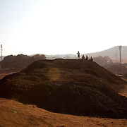 Iron-ore is piled high ready to be loaded on to trucks for delivery to distributors and mills in Keonjhar district known for it's huge reserves of iron-ore. Keonjhar, Orissa, India