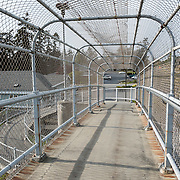A pedestrian ramp spirals up to an enclosed chain link fence overpass over Highway 20 in Coupeville, Washington, USA.